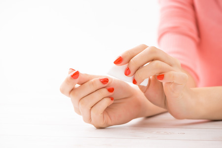 Female hands with manicure and red lacquer on a white table in the beauty salon. closeup of hand of a young woman 스톡 콘텐츠 - 104876390