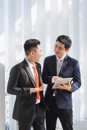 Zwei vietnamesische männliche Mitarbeiter sprechen und lächeln