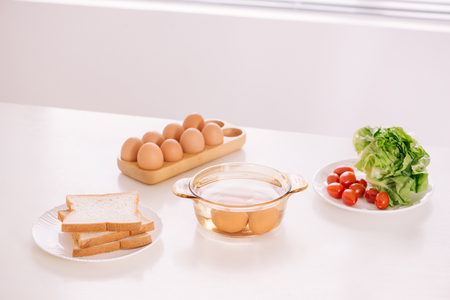 Healthy breakfast consisting of toast, eggs, salad, tomato
