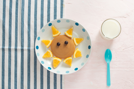 Funny pancakes with orange for kids breakfast