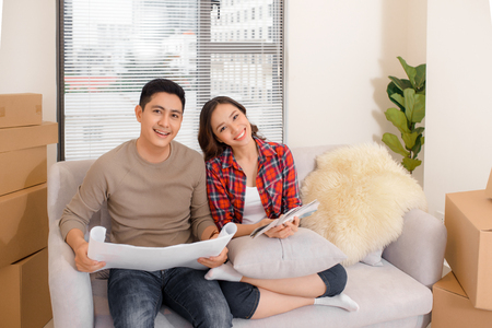 Asian young couple plan interior of new house. They read blueprint near many moving cardboard boxes. Design of decoration at wall and ceiling. First buying home to start family life .