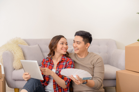 Heureux couple asiatique choisissant les couleurs des murs pour la nouvelle maison