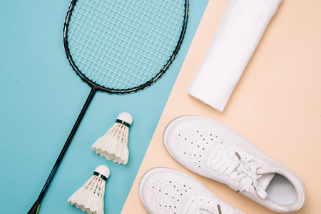 Different sports equipment on pastel color surface