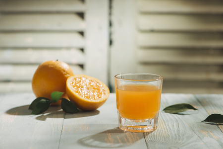 Orange juice and cut oranges on the table 免版税图像