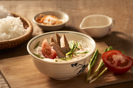 Bun cha ca - one of most popular soup noodle in the seaside area with rice noodle, grilled fish, green onion, tomato and fish sauce... Stock Photo