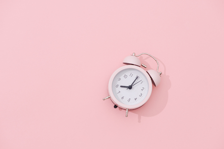 Light pink vintage alarm clock on pink color background 写真素材