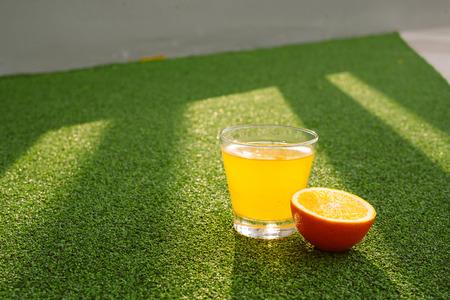 Glass of freshly pressed orange juice and slices of orange on green grass