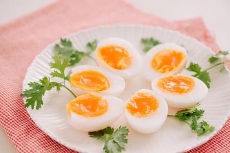 Bouchent la portion d'oeuf de canard à la coque moyenne sur plat blanc Banque d'images