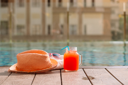 Water-melon fresh fruit smoothie drink with sunglasses and straw hat on swimming pool border - holiday concept