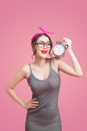 Beautiful smiling young asian woman showing alarm clock on pink Banque d'images