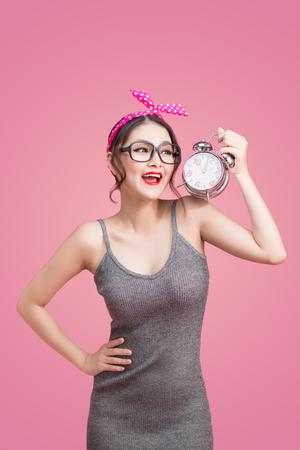 Schöne lächelnde junge asiatische Frau, die Wecker auf Rosa zeigt
