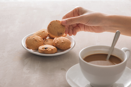 Hand picking cookie from plate. Drink with caffeine or cocoa with milk. Stock Photo