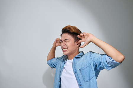 displeased man plugging ears with fingers doesnt want to listen isolated on gray wall background