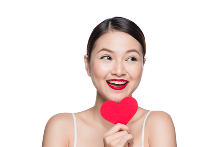 Attractive young woman with red heart. Valentines day art portrait. Perfect make up