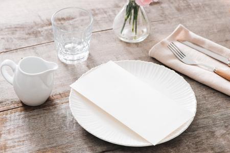 Lente tafeldecoratie met bloemen. Witte platen, vork, mes op houten plaat Stockfoto