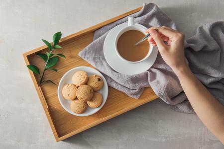 close-up van cookie en hand roeren kopje thee / koffie