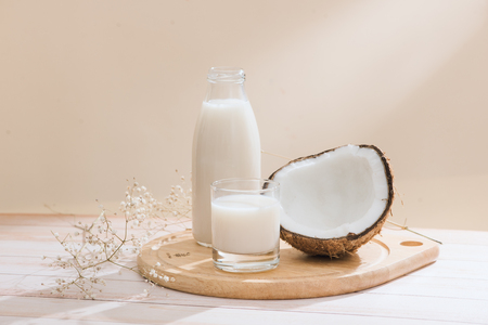 Coconut milk in bottle and glass on table with copy space Banco de Imagens