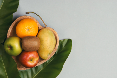 Orange, mango, apple and kiwi in a wooden heart-shaped plate Archivio Fotografico - 105599107