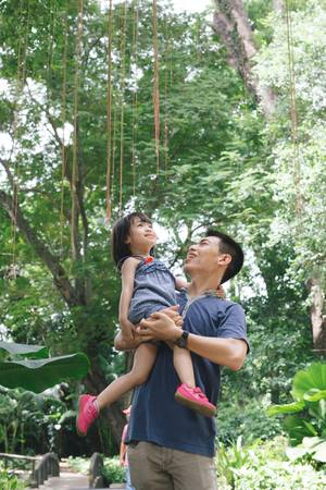 Portrait of little girl hugging her daddy with nature, family concept