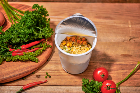 instant noodle, asian fast food, noodle cup on wooden background.