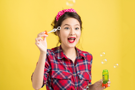 Pin-up asian model blowing soap bubbles over yellow background. Banco de Imagens