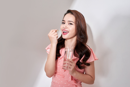beautiful asian women eating vitamin pill for health care at home
