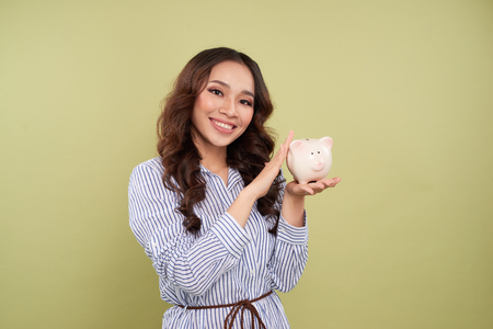 Young woman with a piggy bank on a green background Archivio Fotografico