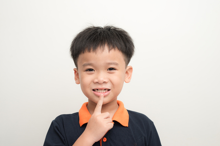 Young happy stylish boy with new tooth instead of missed baby teeth isolated on white background
