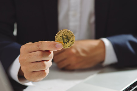 Golden Bitcoin in a Businessman hand