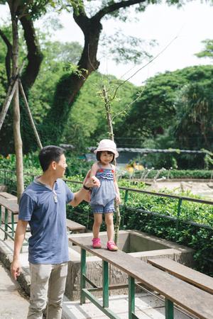 Happy family having fun with animals safari park on warm summer day. Stock Photo
