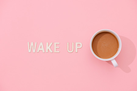 WAKE UP text with a cup of coffee with shadow on pink background. 스톡 콘텐츠