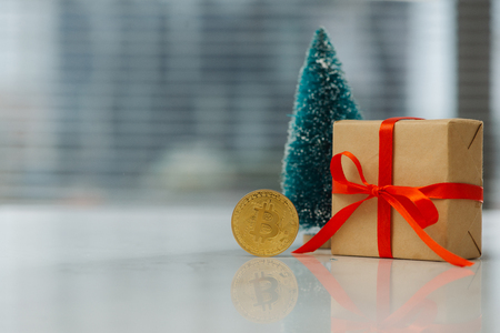 Christmas gift or New Year with ribbon and little fir and best gift bitcoin coin on light background. Stock Photo