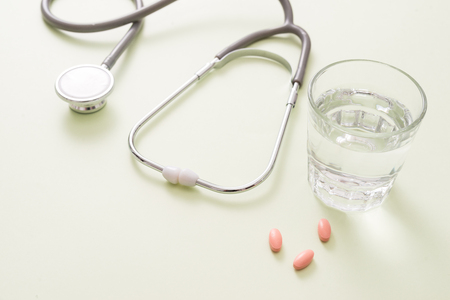 colored pills and a glass of water and stethoscope