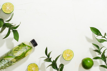 Health care, fitness, healthy nutrition diet concept. Fresh cool lemon rosemary infused water, cocktail, detox drink, lemonade in a glass jar. Light top view flat lay background Banco de Imagens - 106378910