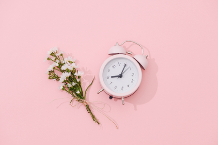 Wildflowers bouquet and retro alarm clock with shadow on pink background Stock Photo