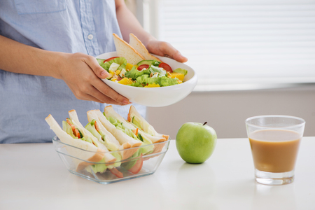 Hands of a woman is making school lunch box. Stock Photo
