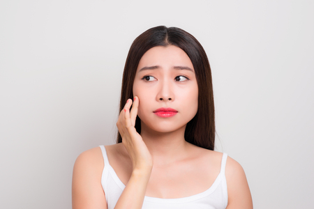 Perfection is a hard work. Acne, pimple, clear and clean, oily, dry skin concept. Cose up cropped photo of worried young lady touching her face gently Stock Photo - 106382164