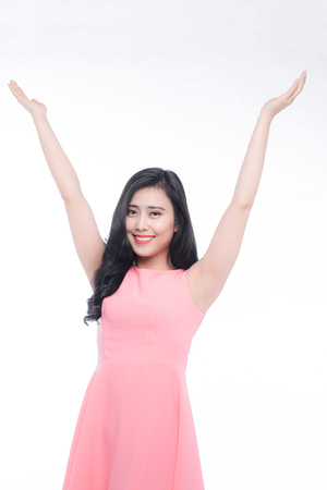 Happy young asian woman raise hands over white. Imagens