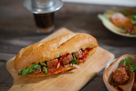 Vietnamese sandwich bread with meatballs in tomato sauce and radish, carrot pickle, cucumber, coriander. Banque d'images
