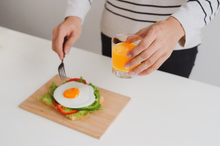 Hands of man cut the eggs on paper, served with bread, herbs, sausage and fresh juice.