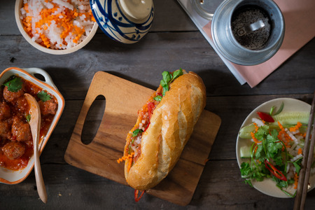 Vietnamese sandwich bread with meatballs in tomato sauce and radish, carrot pickle, cucumber, coriander. 스톡 콘텐츠