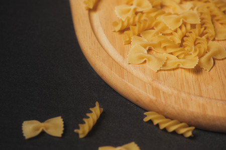 Variety of types and shapes of dry Italian pasta on dark background