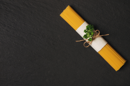 Dry spaghetti pasta tied up with rope on dark wooden table