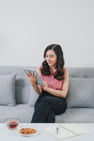 Asian woman on the couch at home doing online shopping, so comfortable, in fashioanble white outfit, so nice light design interior indoors