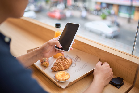 Male searches needed information on internet website via smart phone while sits at terrace cafe with juice and sweet dessert Stock Photo