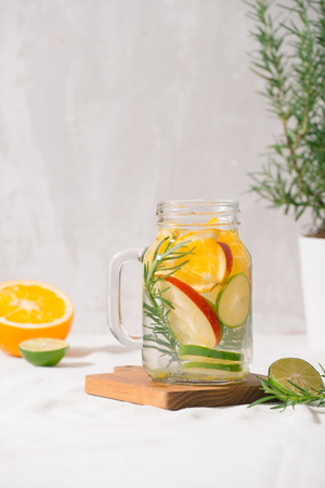 Detox water with lime, organe, apple and rosemary in a mason jar glass with a white wooden background Stock fotó