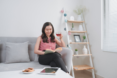 young woman drinking tea while reading a book on the couch Stockfoto