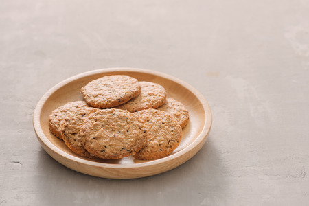 Oat cookies in plate isolated on white background, top view. Sweet bakery products. Round cookies in a wooden plate. 写真素材