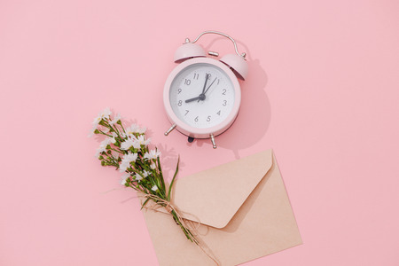 Wildflowers bouquet and retro alarm clock with shadow on pink background 版權商用圖片