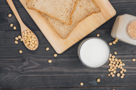 Breakfast with soy beans in spoon, soy milk and sandwich on wooden background